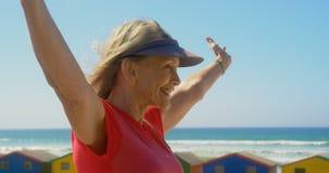 Vista lateral de la situación caucásica mayor activa de la mujer en una 'promenade' en la playa 4k metrajes