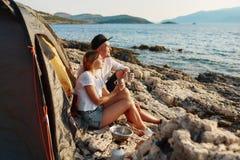 Vista lateral de la tienda cercana relajante de los pares románticos en la playa de la roca imagen de archivo libre de regalías