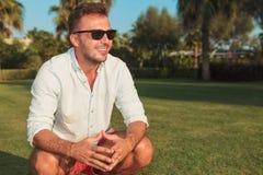 Vista lateral de las gafas de sol que llevan sonrientes agachadas de un hombre Imagen de archivo libre de regalías