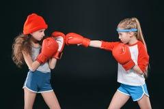 Vista lateral de las muchachas juguetonas que fingen el boxeo aislado en negro Imagenes de archivo
