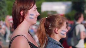 Vista lateral de las muchachas que miran el partido de fútbol el apoyar de la Argentina en zona de la fan metrajes