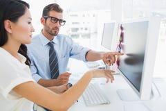 Vista lateral de los editores de fotos casuales que trabajan en el ordenador Foto de archivo