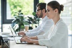 vista lateral de los encargados jovenes concentrados que trabajan con los ordenadores portátiles junto imagen de archivo libre de regalías