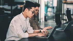 vista lateral de los hombres de negocios multiculturales que trabajan en la tabla con los ordenadores portátiles en moderno imagen de archivo