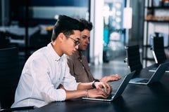 vista lateral de los hombres de negocios multiculturales que trabajan en la tabla con los ordenadores portátiles en moderno fotografía de archivo