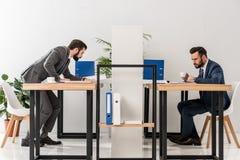 vista lateral de los hombres de negocios que trabajan y que beben el café Imágenes de archivo libres de regalías