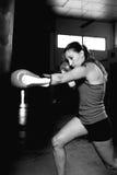 Vista lateral de los movimientos practicantes del boxeador de sexo femenino en gimnasio fotos de archivo libres de regalías