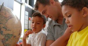 Vista lateral de los niños de enseñanza caucásicos jovenes del profesor de sexo masculino sobre la geografía con el globo en la s almacen de metraje de vídeo
