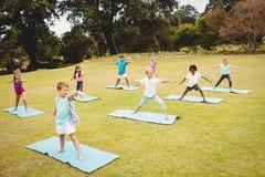 Vista lateral de los niños que hacen yoga Imagen de archivo libre de regalías