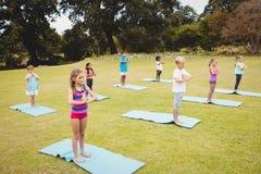 Vista lateral de los niños que hacen yoga Foto de archivo libre de regalías