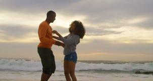 Vista lateral de los pares afroamericanos que se abrazan en la playa 4k almacen de video