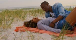 Vista lateral de los pares afroamericanos que se divierten en la playa 4k almacen de metraje de vídeo