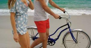 Vista lateral de los pares caucásicos que caminan con la bicicleta en la playa 4k almacen de metraje de vídeo