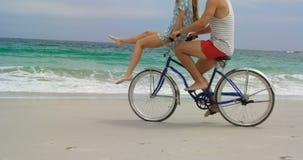 Vista lateral de los pares caucásicos que montan una bicicleta en la playa 4k metrajes