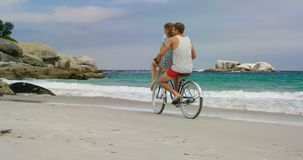 Vista lateral de los pares caucásicos que montan una bicicleta en la playa 4k almacen de metraje de vídeo