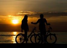 Vista lateral de los pares que se colocan en la costa con sus bicicletas y que disfrutan de puesta del sol fotos de archivo