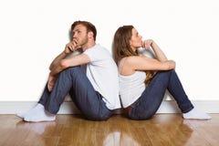 Vista lateral de los pares que se sientan en piso Imagen de archivo