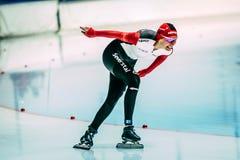 Vista lateral de los patinadores de la velocidad de la muchacha que corren abajo de la curva de la pista Imagenes de archivo