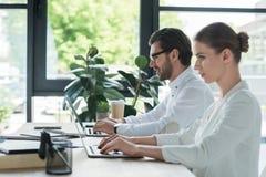 vista lateral de los socios comerciales que trabajan con los ordenadores portátiles junto imagen de archivo
