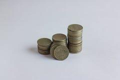 Vista lateral de pilas de monedas que aumentan en altura, en el fondo blanco del estudio Imagen de archivo