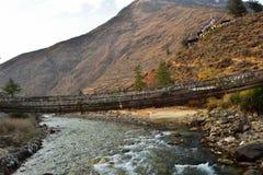 vista lateral de puente colgante que camina con muchas banderas coloridas del rezo en Bhut?n fotos de archivo libres de regalías