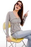 Vista lateral de señalar a la hembra que se sienta en silla Foto de archivo libre de regalías