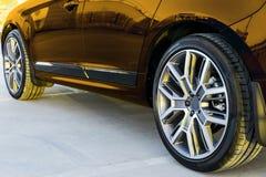 Vista lateral de um carro Roda do pneu e da liga de um carro moderno do ouro na terra no por do sol Detalhes do exterior do carro fotografia de stock