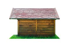 Vista lateral de uma cabana de madeira do cão com um telhado vermelho, estando na grama verde Isolado em um fundo branco com um t imagem de stock