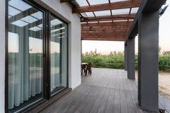 Vista lateral de uma varanda aberta na frente de uma casa de campo moderna da floresta A floresta nova do pinho sob o por do sol  Imagem de Stock Royalty Free