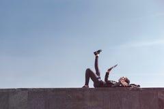 Vista lateral de un adolescente usando la tableta en la mentira de los días de fiesta al aire libre con el cielo claro en fondo C Imagenes de archivo