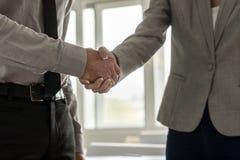 Vista lateral de un apretón de manos de un hombre de negocios y de una empresaria imagen de archivo
