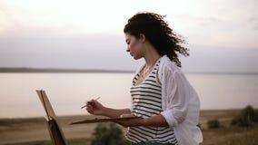Vista lateral de un artista rizado atractivo de la mujer que trabaja en su imagen con el caballete al aire libre cerca del lago M metrajes