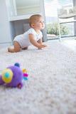 Vista lateral de un bebé que se arrastra en la alfombra Imagen de archivo libre de regalías