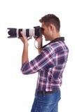 Vista lateral de un fotógrafo joven que toma una foto. Foto de archivo libre de regalías
