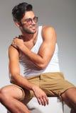 Vista lateral de un hombre asentado con la mano en hombro Fotografía de archivo