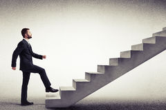 Vista lateral de un hombre en un desgaste formal que sube las escaleras concretas Imagen de archivo