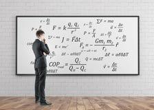Vista lateral de un hombre de negocios pensativo, fórmulas Foto de archivo