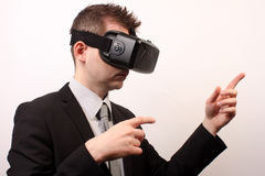 Vista lateral de un hombre que lleva auriculares de la grieta 3D de Oculus de la realidad virtual de VR, tocando o señalando en a Imagen de archivo