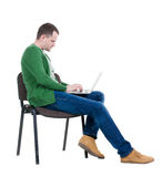 Vista lateral de un hombre que se sienta en una silla para estudiar con un ordenador portátil Imágenes de archivo libres de regalías