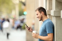 Vista lateral de un hombre que usa un teléfono elegante en la calle Imágenes de archivo libres de regalías