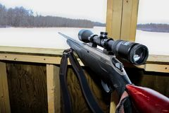 Vista lateral de un rifle en una persiana de la caza imagenes de archivo
