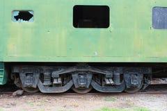 Vista lateral de un vehículo de pasajeros verde viejo del tren con una ventana quebrada, detallando la configuración de la rueda  foto de archivo libre de regalías