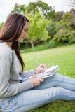 Vista lateral de una chica joven que se sienta en la hierba mientras que escribe encendido Fotografía de archivo