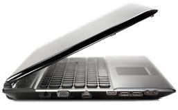 Vista lateral de una computadora portátil moderna negra en una parte posterior del blanco Fotos de archivo