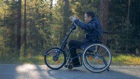 Vista lateral de una manija giratoria del hombre parapléjico de una silla de ruedas móvil del entrenamiento metrajes
