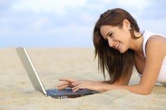 Vista lateral de una muchacha del adolescente que hojea su ordenador portátil que miente en la arena de la playa Fotografía de archivo