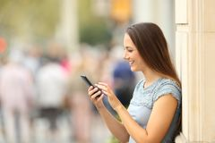 Vista lateral de una muchacha que comprueba un teléfono elegante en la calle Imagen de archivo libre de regalías