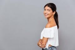 Vista lateral de una muchacha sonriente que se coloca con las manos dobladas Fotos de archivo
