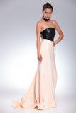 Vista lateral de una mujer atractiva joven en un vestido de noche largo Fotografía de archivo libre de regalías