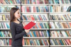 Vista lateral de una mujer con el libro rojo en biblioteca Imágenes de archivo libres de regalías